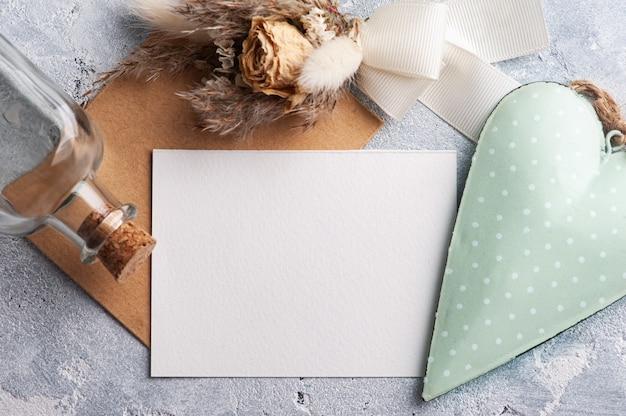 Papel vazio e envelope kraft com coração decorativo verde e flores secas. simulação de casamento na mesa cinza