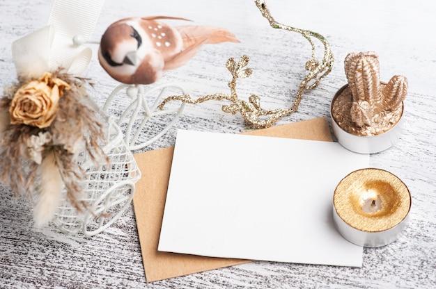 Papel vazio e envelope kraft com decoração em cores neutras. suculenta dourada e decoração em mesa branca. espaço de trabalho moderno
