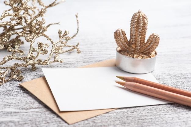 Papel vazio e envelope kraft com lápis de cores neutras. suculenta dourada e decoração em mesa branca. espaço de trabalho moderno