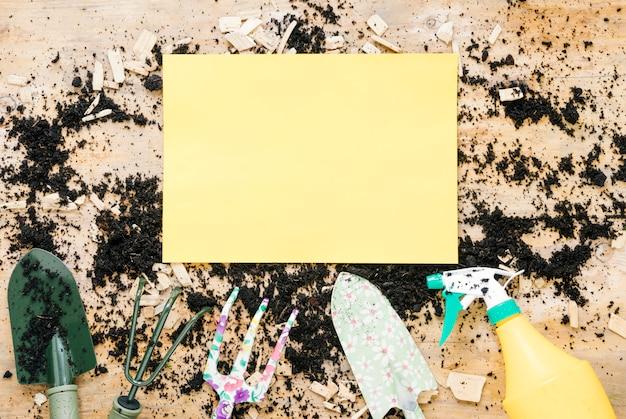 Papel vazio em branco amarelo sobre solo com equipamentos de jardinagem