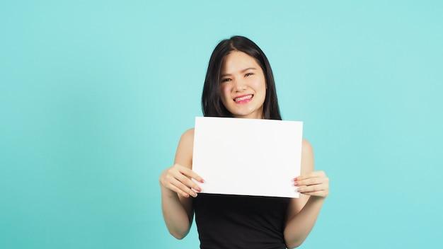 Papel vazio em branco na mão de uma mulher asiática em fundo verde menta ou azul tiffany.