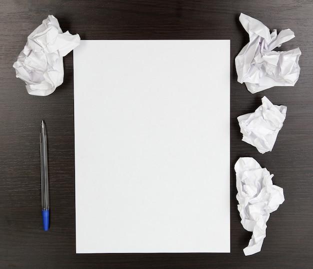 Papel vazio, papel amassado e caneta na mesa de madeira
