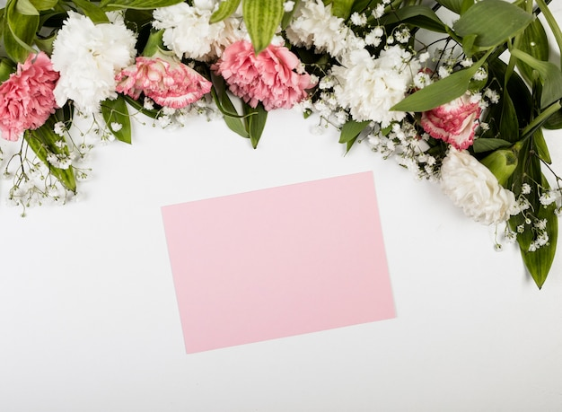 Papel vazio rosa e buquê de flores