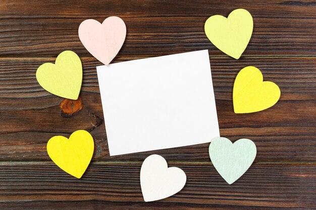 Papel vazio sobre fundo de madeira com coração colorido no dia dos namorados