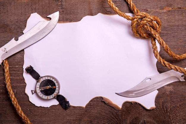 Papel velho com bússola, faca e corda na mesa de madeira vintage. vista superior do espaço vazio para o seu texto.