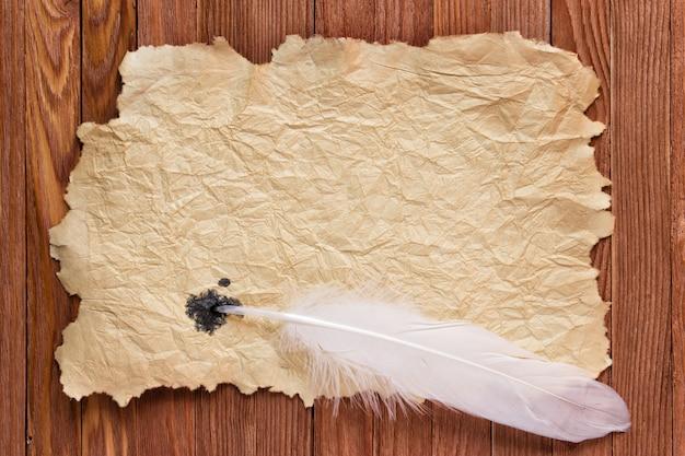Papel velho de textura e pena branca em cima da mesa