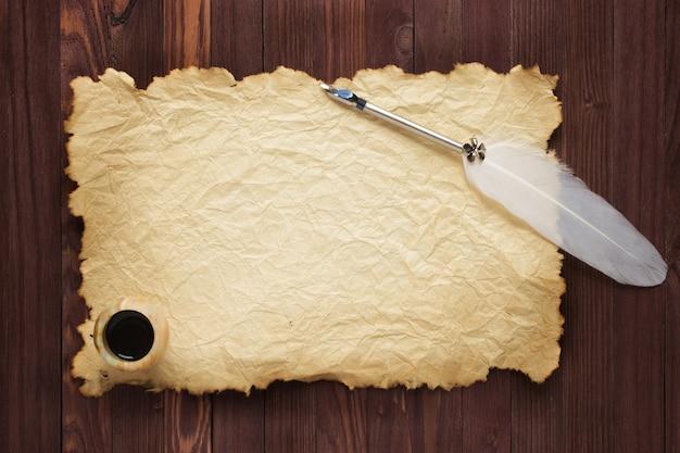 Papel velho e tinteiro com caneta de pena em uma superfície de madeira