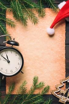 Papel velho em branco com galhos de árvore de abeto de natal com despertador vintage, caixas de presente, veados e chapéu de papai noel.