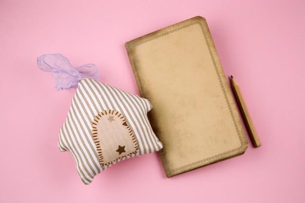 Papel velho vintage de vista superior, lápis e casa de brinquedo de pelúcia em um fundo rosa pastel