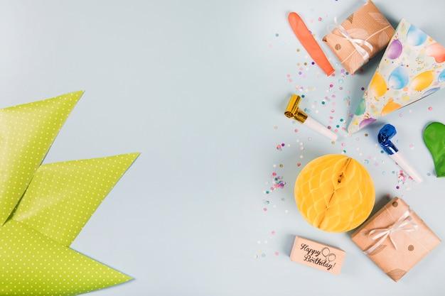 Papel verde triangular e itens de festa em fundo cinza