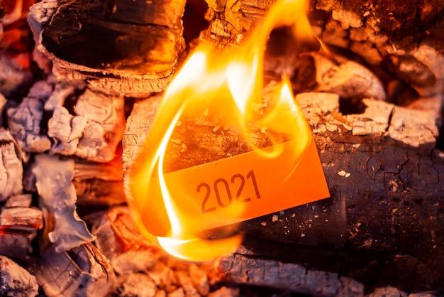 Papel vermelho com a inscrição 2021 queimando no fogo