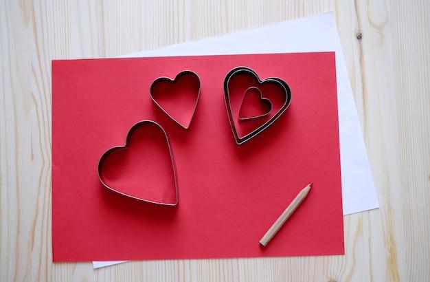 Papel vermelho e branco com formas de coração para cartão feito à mão do dia dos namorados no fundo da mesa de madeira
