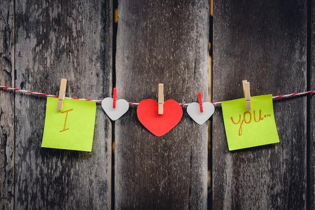 Papel vermelho em forma de coração e palavras de amor