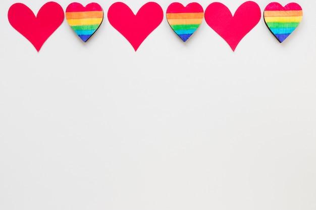 Papel vermelho pequeno e corações de arco-íris na mesa