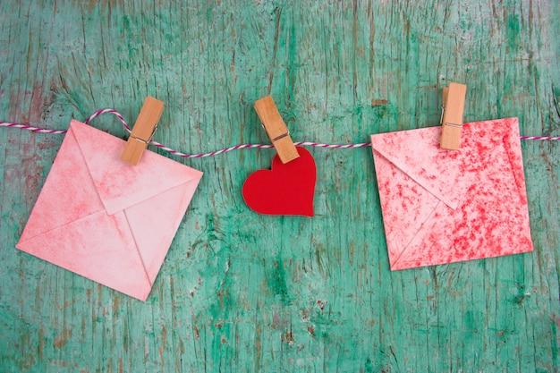 Papel vintage vermelho envelopes e papel coração vermelho pendurado em prendedores de roupa em uma corda