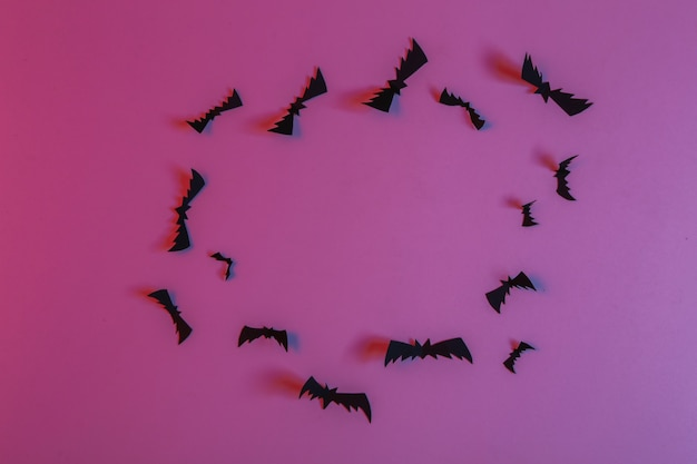 Papel voador cortou morcegos em luz neon rosa azul neon. tema de halloween