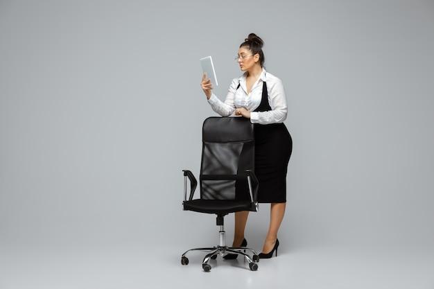 Papelada. jovem mulher em trajes de escritório. personagem feminina bodypositive, feminismo, amar a si mesma, conceito de beleza. mulher de negócios plus size com tablet. chefe, linda garota. inclusão, diversidade.