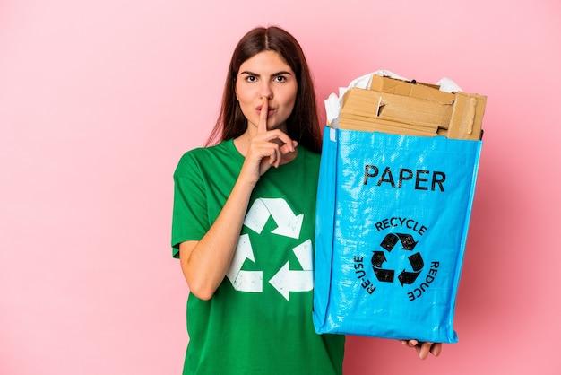Papelão reciclado jovem mulher caucasiana, isolado no fundo rosa, mantendo um segredo ou pedindo silêncio.