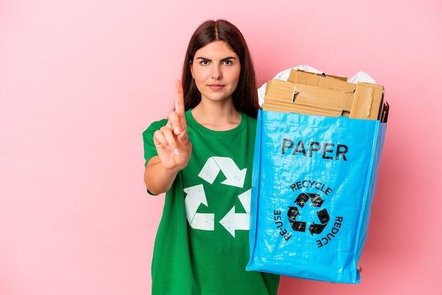Papelão reciclado jovem mulher caucasiana, isolado no fundo rosa, mostrando o número um com o dedo.