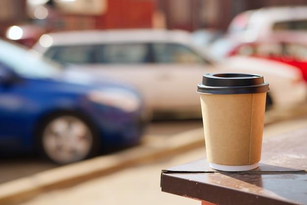 Papelão xícara de café no peitoril da janela. estacionamento turva