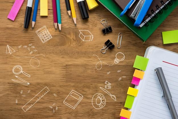 Papelaria colorida no fundo da mesa de madeira com desenhos de doodle