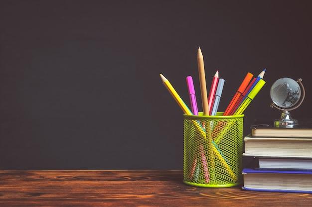 Papelaria em vidro metálico com lápis ao lado de livros com espaço de cópia
