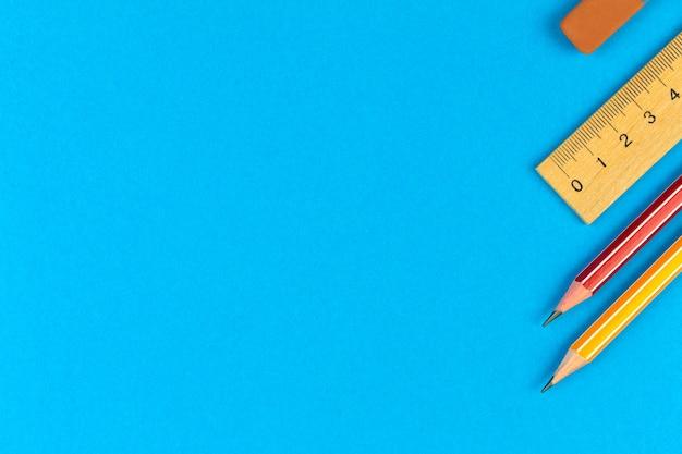 Papelaria escolar com lápis e régua de madeira, composição da borda, plano de fundo plano, área de trabalho azul com espaço de cópia, foto de vista superior