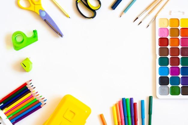 Papelaria para a escola e trabalho criativo em um fundo branco, lay-out plana, vista de cima, espaço de cópia