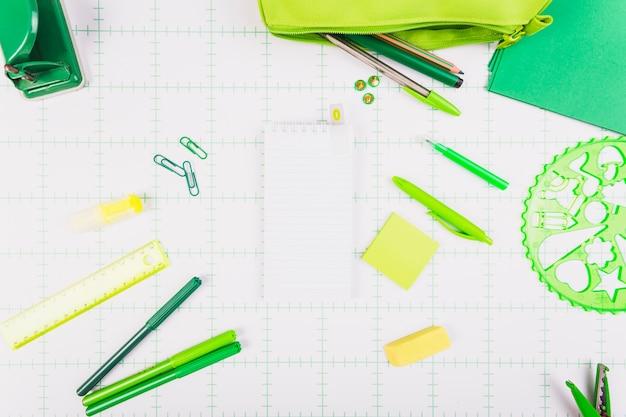 Papelaria verde em torno do bloco de notas