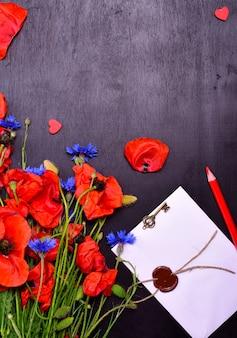 Papoilas vermelhas e flores azuis com um envelope selado