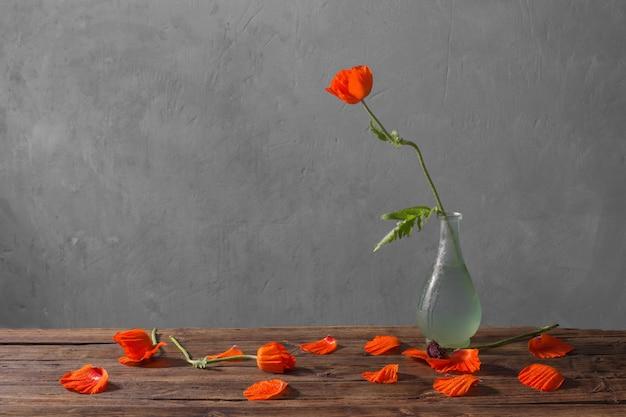 Papoilas vermelhas em um vaso na mesa de madeira
