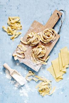 Pappardelle, fettuccine ou tagliatelle italianos amarelos crus da massa, fim acima. ovo macarrão caseiro processo de cozimento, macarrão longo enrolado, espaguete cru.