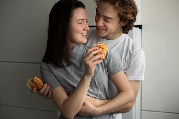 Par, abraçando, segurando, croissants