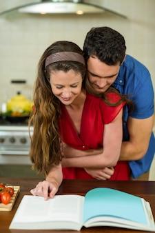 Par, abraçar, em, cozinha, enquanto, verificar, a, receita, livro