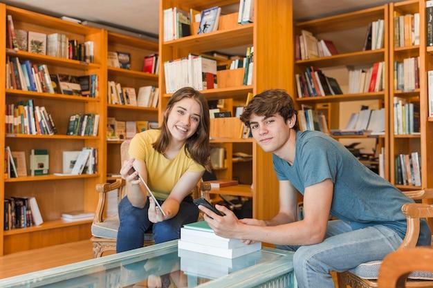 Par adolescente, com, dispositivos, em, biblioteca