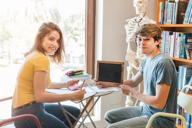 Par adolescente, com, quadro-negro, fazendo, dever casa