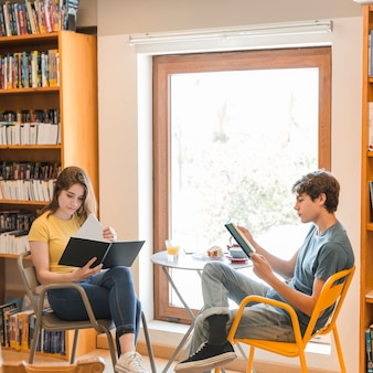 Par adolescente, leitura, em, biblioteca