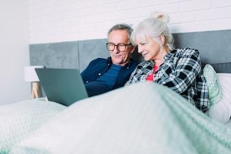 Par ancião, cama, com, laptop