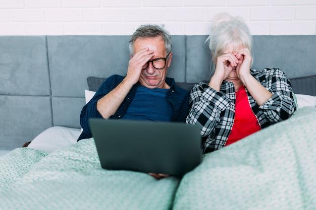 Par ancião, com, dor de cabeça, cama, com, laptop