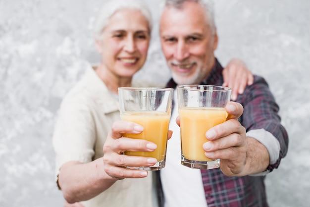 Par ancião, segurando, suco laranja