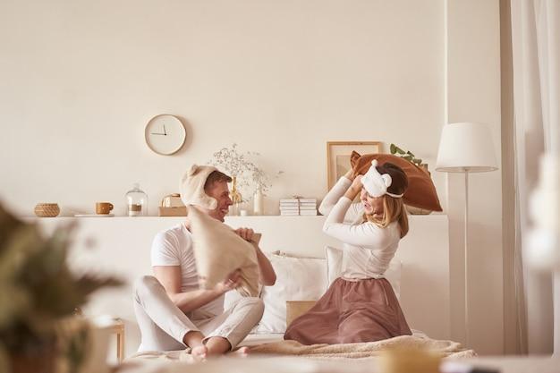Par apaixonado rindo e brincando na cama. homem e mulher lutam almofadas. jovem casal feliz bate os travesseiros na cama em um quarto em casa