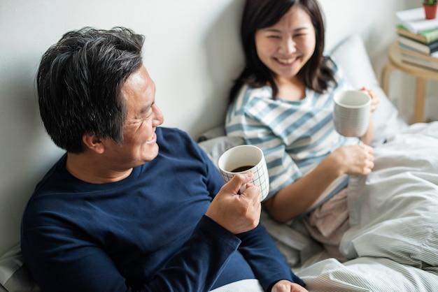 Par asiático, café bebendo, cama