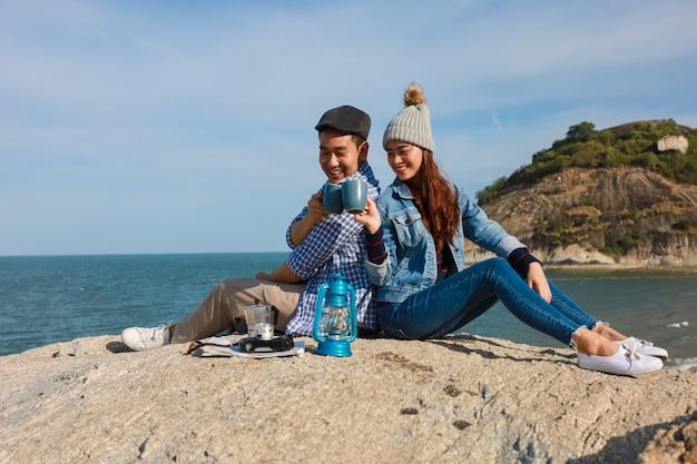 Par asiático, em, camisa azul, com, copo café, e, câmera vintage, piquenique, ligado, a, montanha, perto, a, praia, mar, vista, feliz, e, sorrizo, rosto