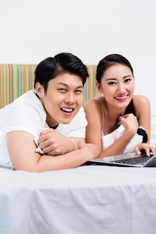 Par asiático, em, quarto, navegar, a, internet, com, computador