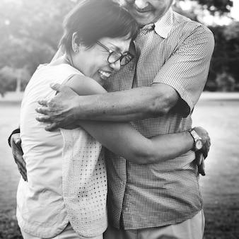 Par asiático sênior, abraçando, um ao outro