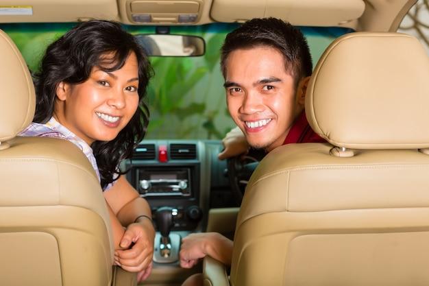Par asiático, sentando, carro