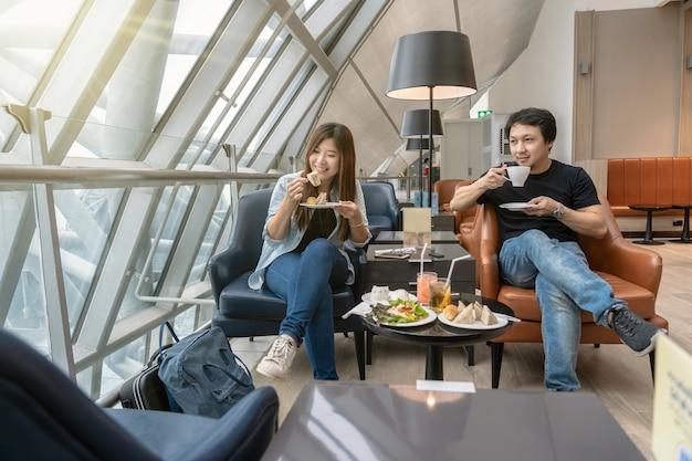 Par asiático, sentando, e, eatting, inn, saguão aeroporto, enquanto, esperando, a, vôo