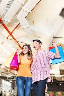 Par asiático, shopping, em, loja moda, ou, loja