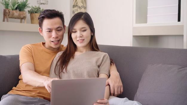 Par asiático, usando computador portátil, para, busca, teia, em, sala de estar, casa