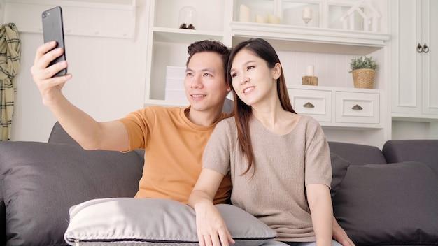 Par asiático, usando, smartphone, para, selfie, em, sala de estar, casa